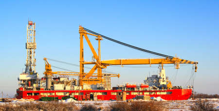 The sea floating crane standing in the winter about river bank Stock Photo