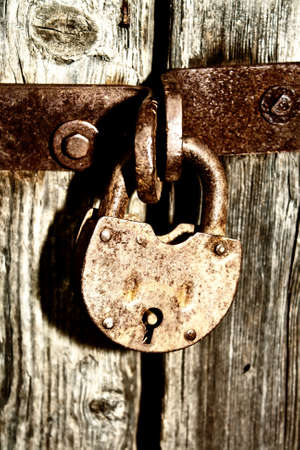 The stylized photo of the old lock on a wooden door symbolizing closeness and inaccessibility Stock Photo