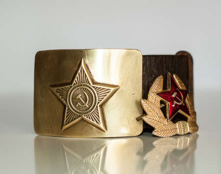 Old soviet soldiers belt with brass buckle and cap badge with a star photo
