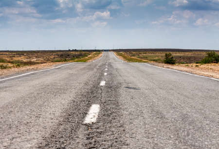 Old empty asphalt road on a red-hot summer sun Stock Photo