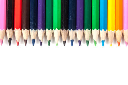 Coloured pencils lying in a row isolated on white background Stock Photo
