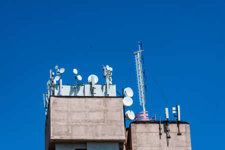 Cellular antenna on the roof of the building against the blue sky Stock Photo