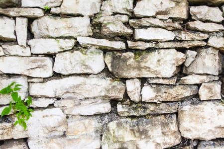 A wall built of rough mountain wild stone white-washed white