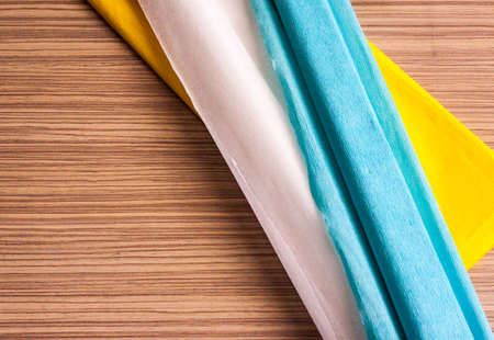 Multi-colored crepe paper lies on the surface of the table Stock Photo