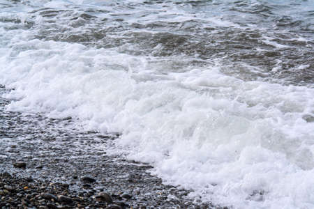 Turbulent sea waves roll on the shore of pebbles