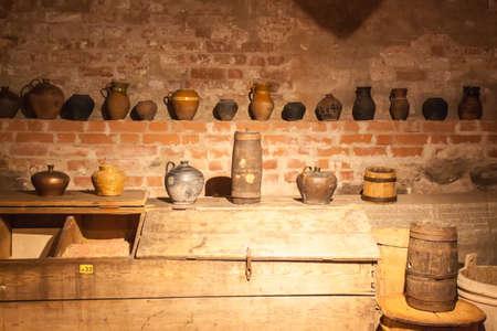 Old crockery standing on shelves in a brick basement