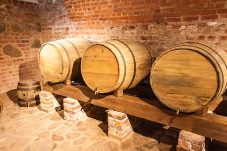 Wooden wine barrel standing in a brick basement on the stand