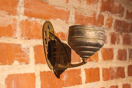 Old wall lamp hanging on brick wall