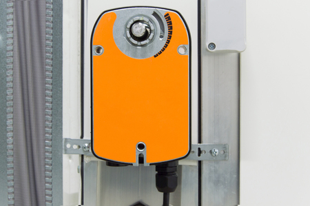 Closeup photo of the orange damper actuator installed on the industrial ventilation unit body, front view
