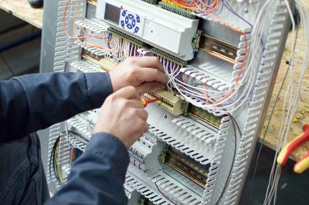 Techniker, der die Niederspannung zusammenbaut industrielles Bedienfeld in der Werkstatt zusammenbaut. Nahaufnahmefoto der Hände.