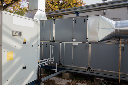 Side view of the industrial air handling unit with DX coil with big condensing unit standing outdoor on the ground covered by fallen leaves Stock Photo