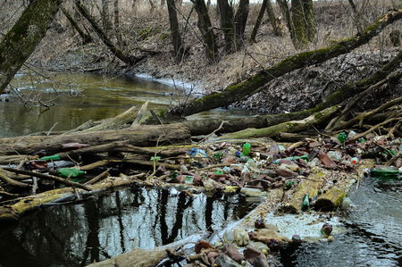 View of the polluted small river with a lot of different plastic garbage. Environment pollution problem