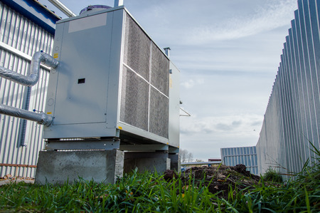 Low angle view of the commercial chiller standing outdoor on the ground near to the modern works building Stok Fotoğraf