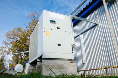 Low angle view of the industrial cooling unit standing outdoor on the ground near to the modern of the factory building Stock Photo