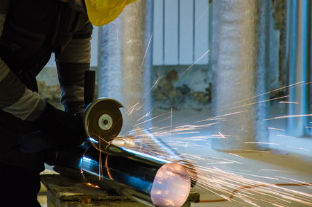 HVAC worker cutting metallic ductwork with the angle grinder