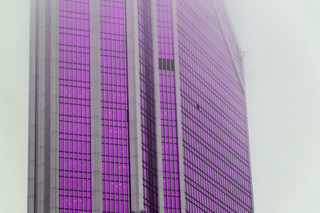 Futuristic photography of the facade of the skyscraper with ultra violet windows standing in the fog