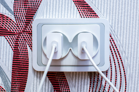 Two modern cell phone chargers plugged into the socket. Energy waste concept. Stock Photo