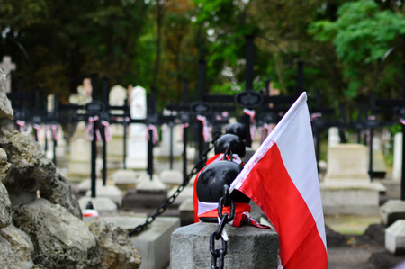 Small Polish flag on the cemetery. National memory day concept.