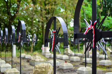 Ribbon with national colours of Poland tied up to the cross on the cemetery. Uprising concept. Stock Photo
