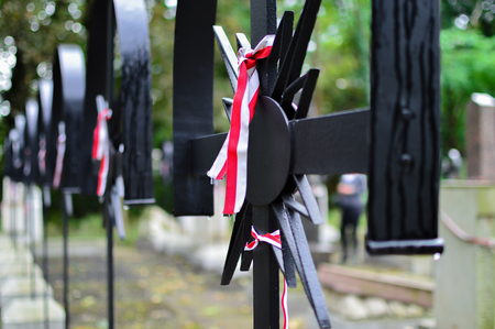 Ribbon with national colours of Poland tied up to the cross on the cemetery. History concept. Stock fotó