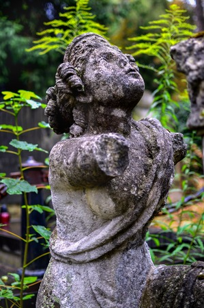 Side view of the ancient female statue with no hands installed on the abbadoned grave Stock Photo
