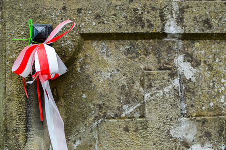 Ribbon with national colours of Poland tied up to the old gravestone on the cemetery. All saints day concept.