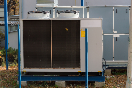 Gray cooling unit for central ventilation system with big ventilation unit standing outdoor on the ground covered by fallen leaves Stock Photo