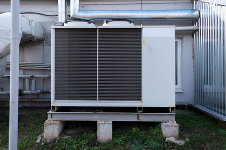 Gray cooling unit for central ventilation system with big ventilation unit standing outdoor on the ground