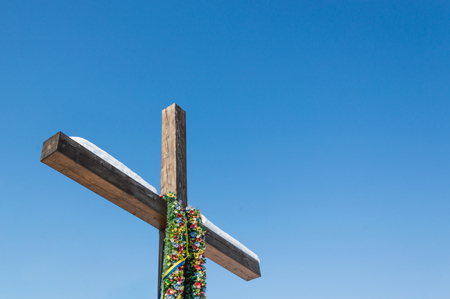 Wooden christian cross with Ukrainian flag color ribbons on the blue sky background, Concept of hope, freedom, rebellion, nationalism, patriotism.