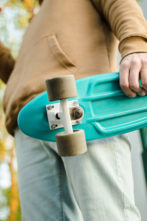 Side view of the young man holding his blue plastic penny board . The concept of modern culture, penny skateboarding, outdoor activity, modern lifestyle.