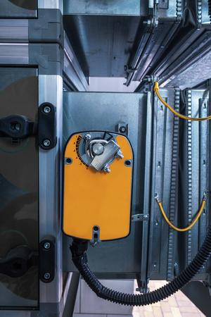 Two industrial orange damper actuators installed on the air handling unit Reklamní fotografie