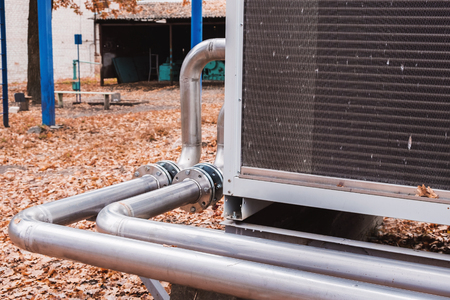 Industrial stainless steel pipes connected to the commercial cooling unit for the HVAC systems