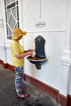 KARLOVY VARY, CZECH REPUBLIC - AUGUST 04, 2018 Woman filling the cup with mineral water from the Lower castle spring, the 3d mineral spring in Karlovy Vary