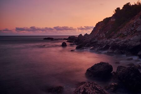 Long exposure photography of the sea waves splashing near to the clif when the sun is going down. Stockfoto