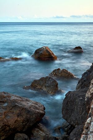 Long exposure photography of the sea waves moving in the rocks