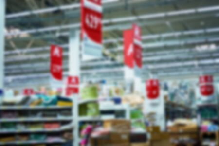 Defocused photo of the people walking inside the light and modern supermarket. Can be used for advertising, presentations and motion design as a background.