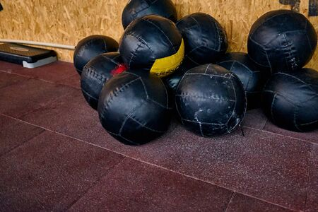 Pile of crossfit wall balls near to the wall. The balls are using for the wall-ball exercise.
