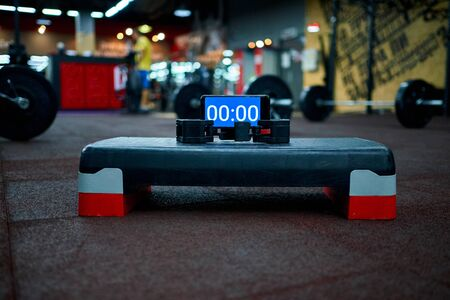 Timer on the stepper platform in the gym before the athlete starts to record video for online qualifier for international crossfit competition. 写真素材