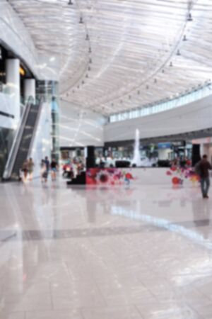 Blurred photo of the people walking inside the light and modern shopping mall centre. Can be used for advertising, presentations and motion design as a background.