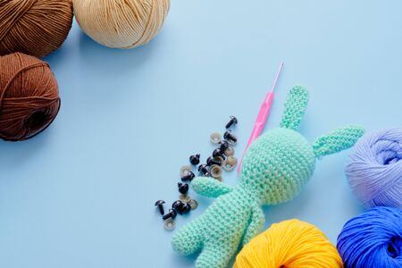 Bright color yarn clews with pastel green stuffed bunny on the blue background. Concept of amigurumi toy making, handycraft, knitting, hobbie. Stockfoto