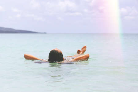 Young Tourist Caucasian Girl Swimming in the Crystal Cear Ocean.