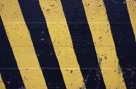 コンクリートの壁に黒と黄色のストライプ