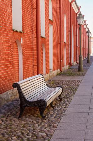赤の壁の近くの白いベンチ