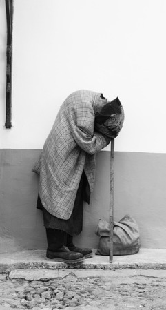 The image of the old, poor woman, which stands near the wall Stock Photo