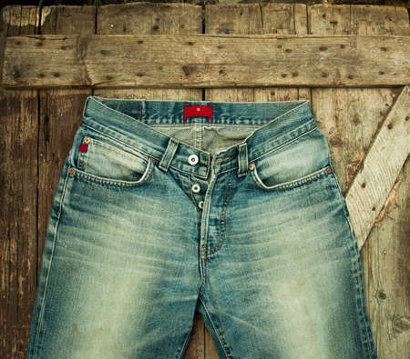 Old jeans on a wooden background