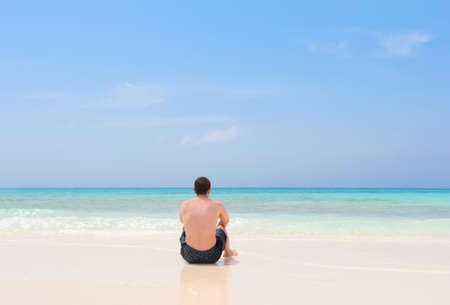 absent: Young man sitting alone on a tropical beach of archipelago Los Roques, Venezuela