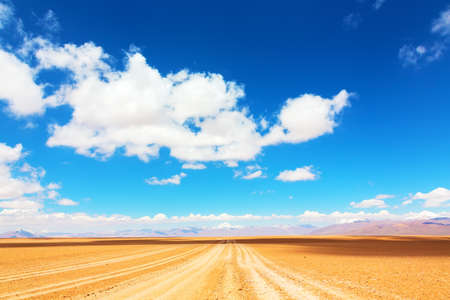 unpaved road: Unpaved road leading straight to a mountains range