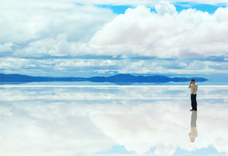 salt flat: Man talking on the mobile phone in the middle of lake with water Stock Photo
