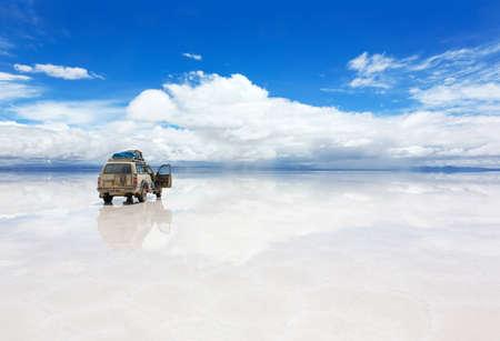Fahrzeug auf der reflektierten Oberfläche des Salar de Uyuni See in Bolivien