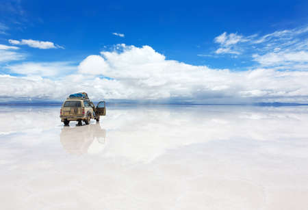 unruffled: vehicle on the reflected surface of Salar de Uyuni lake in Bolivia